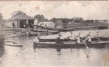 """Photo: Odense Roklub 1904. Postkort. Sandsynligvis fra indvielsen af klubben. Der optræder 3 både på billedet, og det var det antal af både roklubben rådede over på dette tidspunkt. I baggrunden anes en etageejendom - kaldet """"Vanløse""""."""