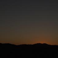Sun coming up over a desert landscape