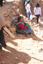 "Photo: This woman has rented this ""mine"" from the local priest and in turn collects money from all who wish to take rocks from her hole. My language helper told me that the censer next to her is her own offering to Pachamama, asking for many customers."