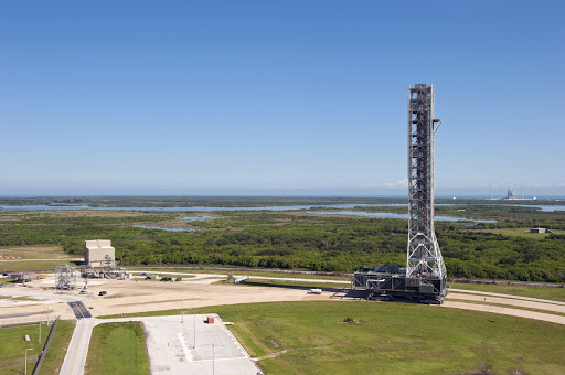 A crawler-transporter moves NASA's new mobile launcher to the Mobile Launcher east park site.