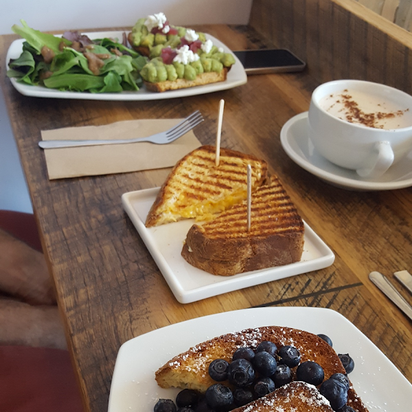 From left to right: 1) avocado toast topped with pickled onions & goat cheese served with a side salad, 2) three-cheese grilled cheese, 3) Overnight French toast with blueberries