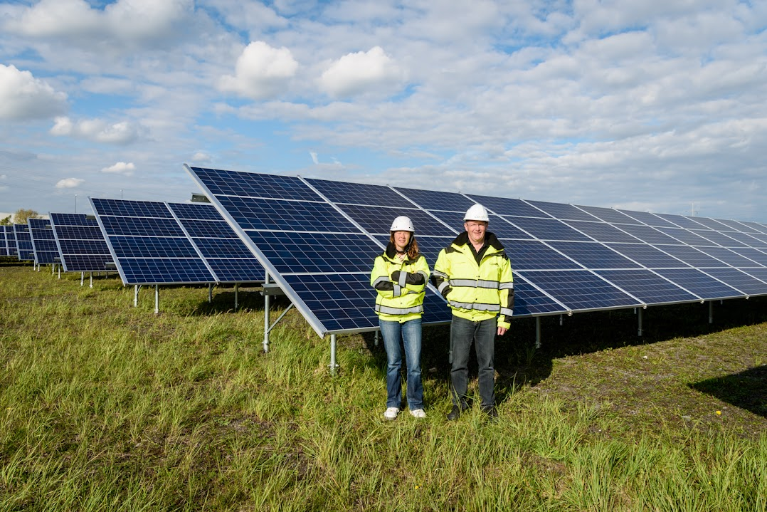 Two people stand in front of large solar panels in a field.
