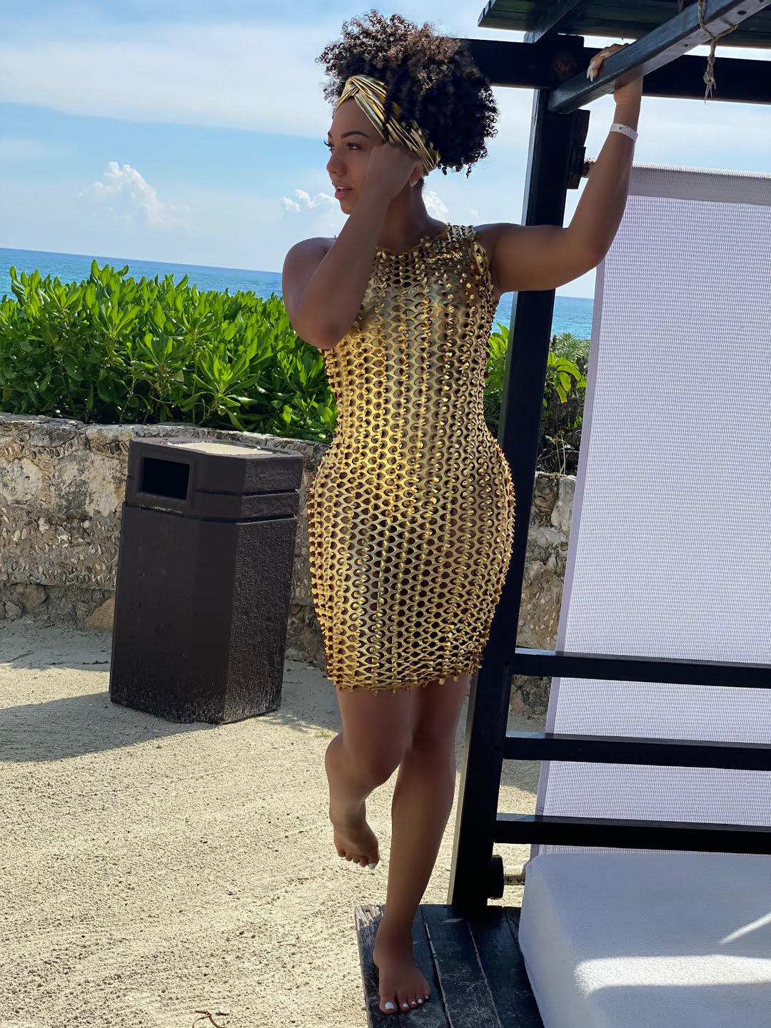 dr eva leaning on a cabana gold stretchy beach cover up dress
