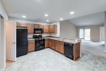 Fully-equipped kitchen with wood cabinets and black appliances
