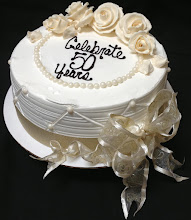 Photo: Vintage Anniversary Cake: white base w/ivory whipped cream roses, edible pearl studs, and ivory ribbon wrap w/bow. Horizontal grooves around sides w/quilting overlay.