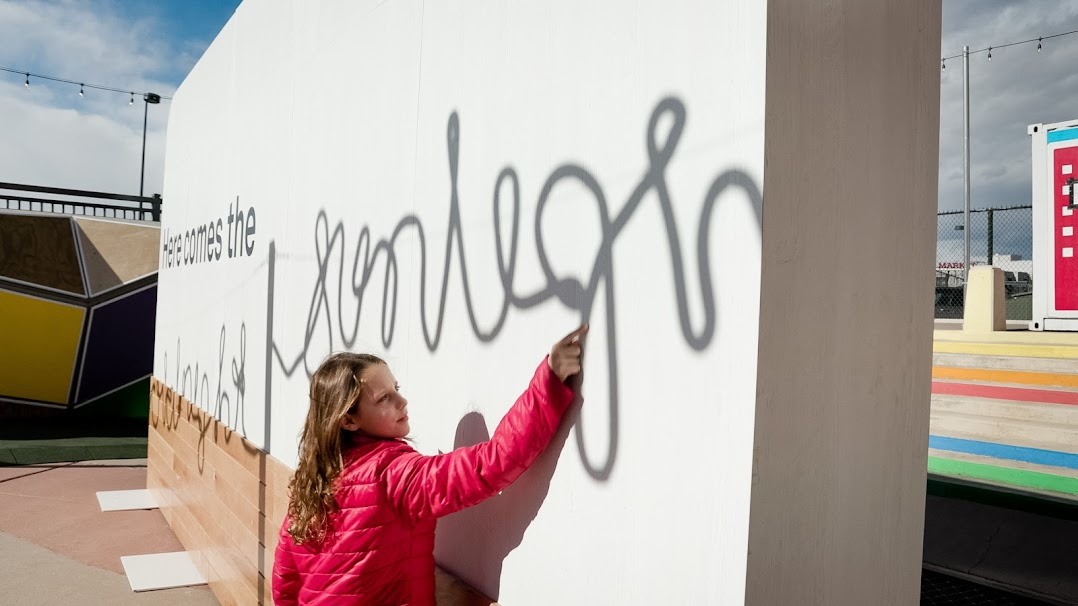 デンバーのダウンタウンに期間限定で設置された構築物の壁に触れる若者。この構築物は、寒い季節に光熱費を払えない多くの人々がいることを伝えています。