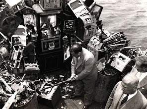 "Photo: ""Aboard a police boat on October 10, 1934, New York Mayor Fiorello LaGuardia hacks away at confiscated slot machines about to be destroyed and dumped into New York harbor."""