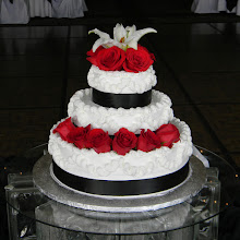 Photo: Classy Wedding Cake: 3-tiers frosted in white, Italian whipped cream. Decor: Lisa's traditional border with black satin ribbon wrapped around bottom of each tier. Fresh red roses & large Calla Lilies complete this timeless look.