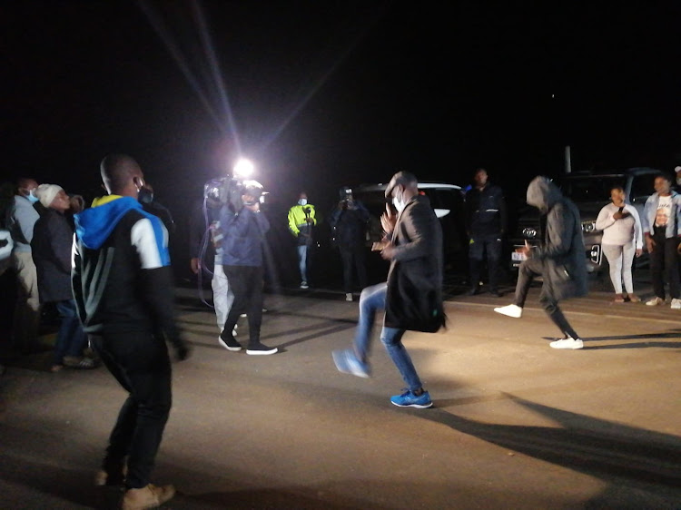 Supporters of former president Jacob Zuma sing struggle songs outside his homestead in Nkandla on Wednesday night. Zuma's son, Edward Zuma, vowed that police would not be allowed in should they arrive to make an arrest.