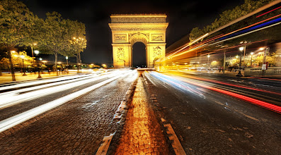 Photo: Arc de Triomphe in Paris, France  This is a dangerous spot!  But so pretty... It was a cool night in Paris.  It was a bit damp too, as if it might rain at any moment.  So that kept me moving from spot to spot pretty quickly.  I was secretly hoping for a bit of rain... Europe at night in a light rain is always kind of charming.  I'm pretty sure that locals don't find it charming... just annoying.    from the blog www.stuckincustoms.com