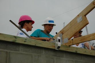 Photo: Site Supervisor Kristi Thum, center, guiding two volunteers in securing the truss.