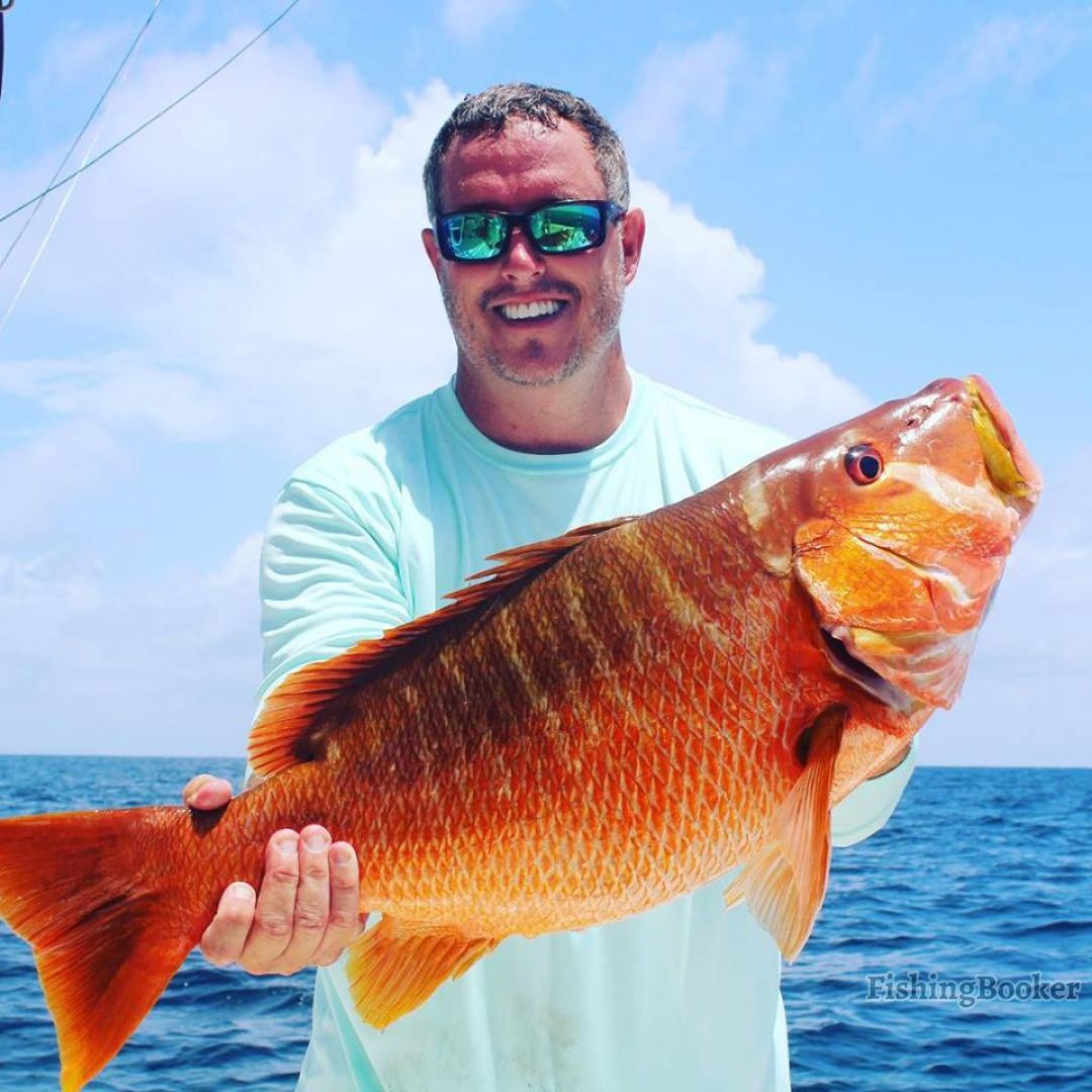 Belize bottom fishing: An angler holding a big Grouper