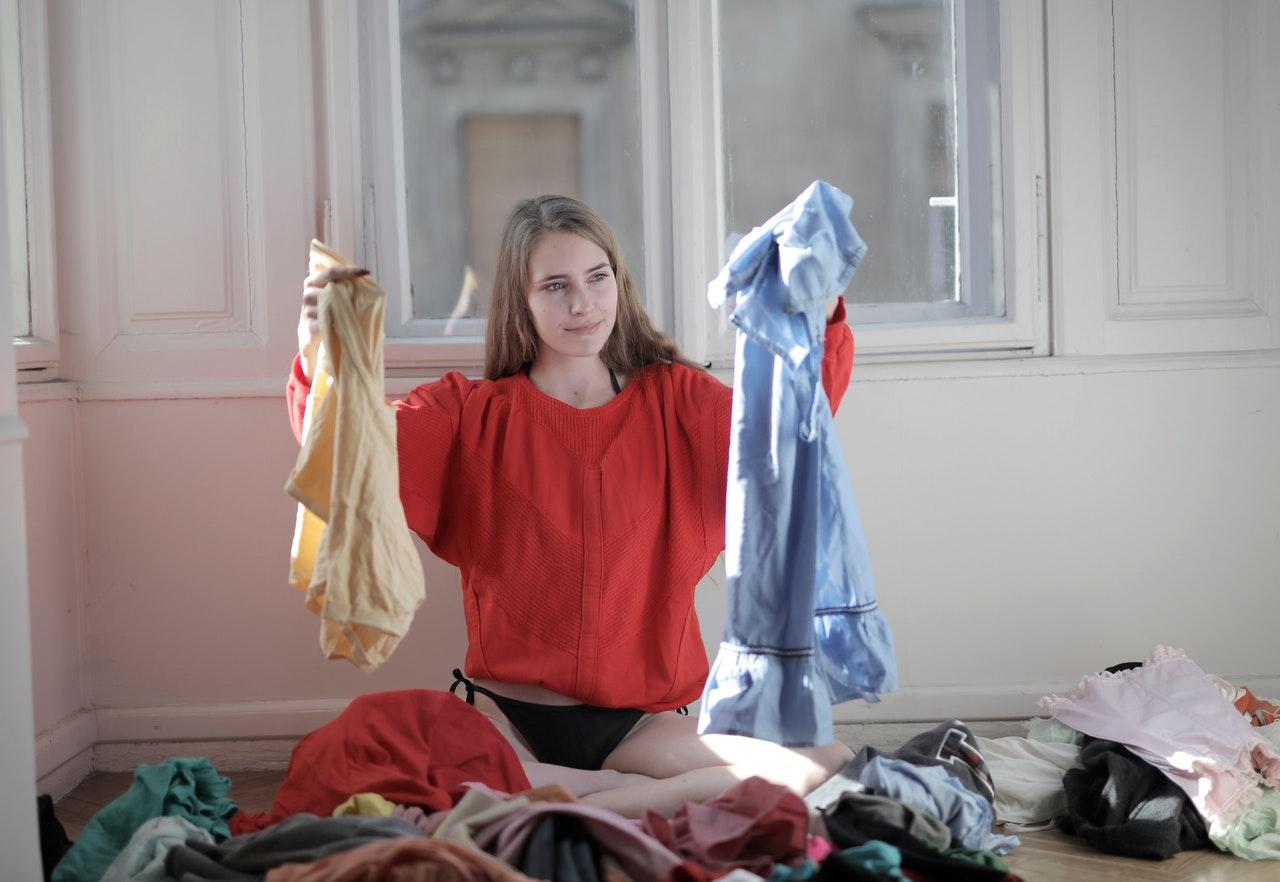 Uma mulher sentada segurando peças de roupas com outras jogadas pelo cbão.