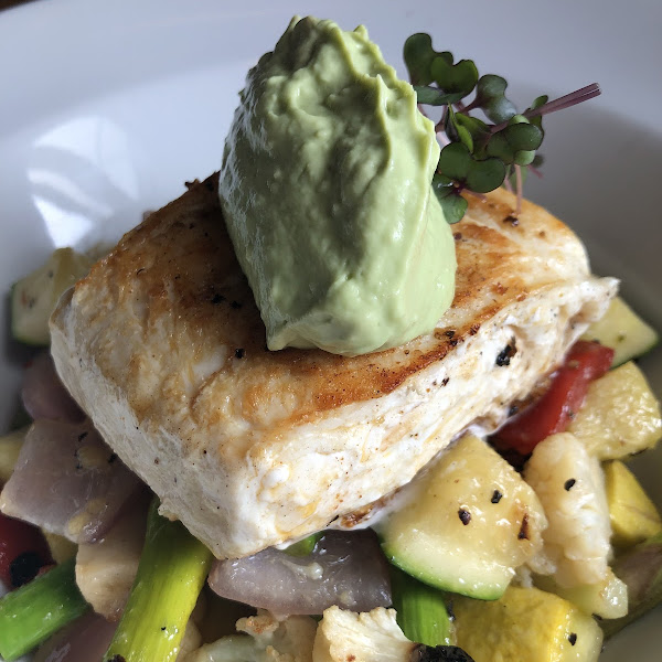 Pan seared halibut over roasted veggies with an avocado cream.