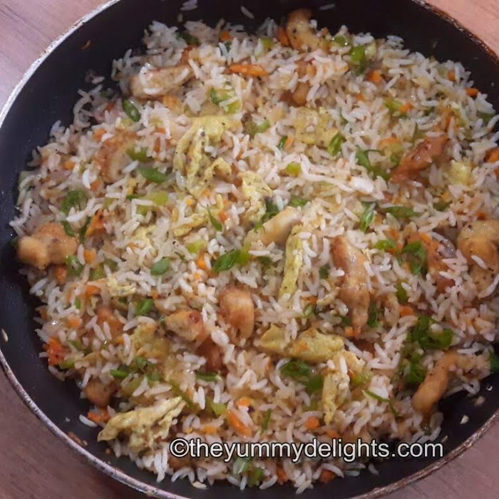 close up photo of chicken fried rice in a pan garnished with spring onion greens