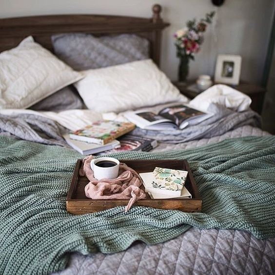 Fall inspired bedroom decor bed with many blankets blue comforter and green throw blanket.