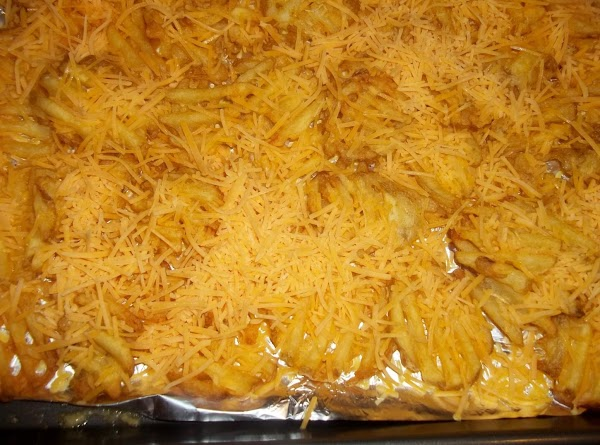 Sprinkle 1 cup of the cheese evenly over the hot fries.