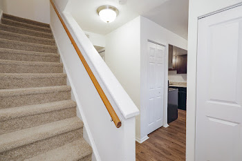 Townhome stairs, hallway, and view of kitchen