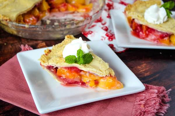 Slice Of Blushing Peach Pie On A Plate.
