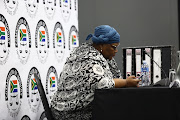 Vytjie Mentor looks at her phone before the start of her cross examining about the testimony at the state capture commission.
