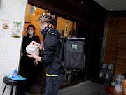 Japan's Olympic fencing medallist Ryo Miyake collects a ramen noodle order from a restaurant as he works his part-time job as Uber Eats delivery person under a nationwide state of emergency as the spread of the coronavirus disease (Covid-19) continues in Tokyo, Japan May 12, 2020.