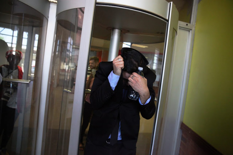 Former Parktown boys assistant water polo coach Colin Rex hides his face after leaving the high court sitting at the Palm Ridge Magistrate's Court, South of Johannesburg.