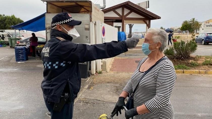 Un Policía Local le toma la temperatura a una mujer en la entrada del mercadillo de Garrucha