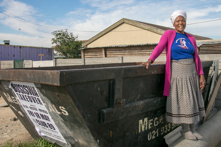 Ma Agnes stands by her container where she collects over 15,000kg of glass every month thanks to her business savvy and hard work.
