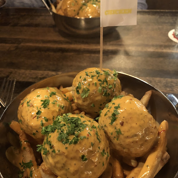 Chicken meatballs with crack sauce over fries.