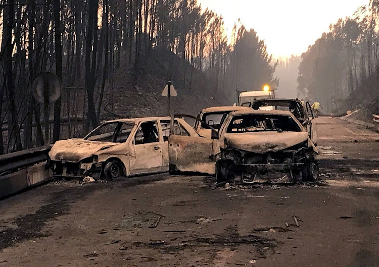 Burned cars are seen on a local road during a forest fire near Pedrogao Grande, Portugal, on Sunday. Picture: REUTERS