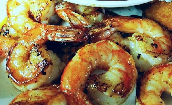 Thread your shrimp on skewers, then combine the juice and honey. Brush onto both...