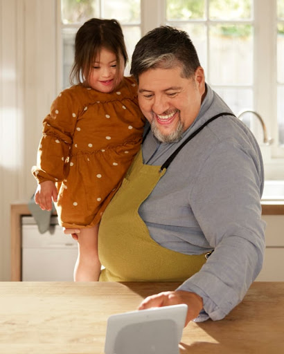 The father holds his toddler daughter in the kitchen and touches the Nest Hub display as they prepare a recipe.