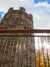 Photo: Sunlight on metal fence in front of a stone tower at Hills and Dales Metropark in Dayton, Ohio.