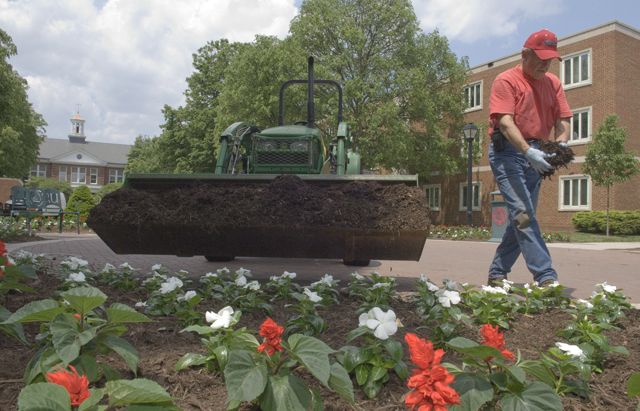 Photo: Carvel Brumfield puts finishing touches on a flower bed as he helps get campus ready for Commencement.