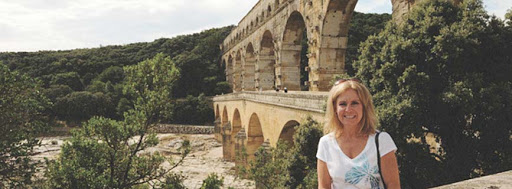 A visitor poses in the front of the ancient Roman aqueduct bridge, Pont du Gard, crossing the Gardon River in southern France.