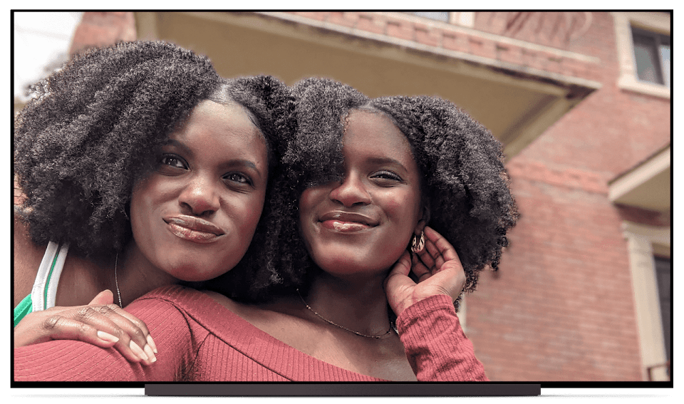 A photo of two women taking a selfie. That same photo transitions onto the screen of a TV, to show how you can enjoy Google Photos on your TV screen.