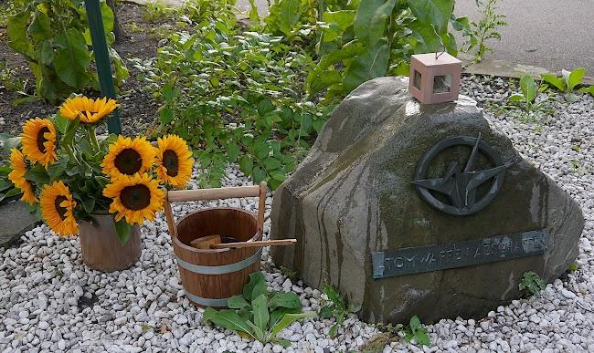 Gedenksten «Atomwaffen abschaffen», darauf ein Holzkästchen, links daneben ein Holzeimer mit Bambuskelle (zum Benetzen des Gedenksteins) und ein Sonnenblumenstrauß im Tonkrug.