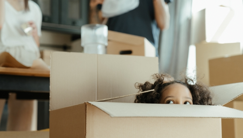 a little girl plays in a moving box while her parents pack in the background