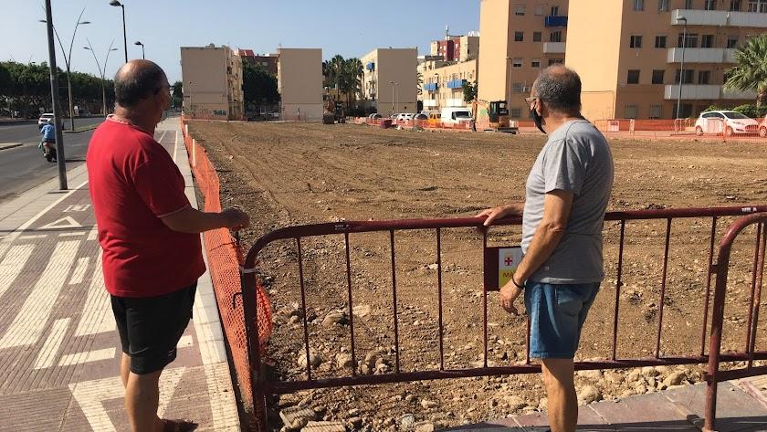 Dos almerienses miran unas obras junto a la Avenida del Mediterráneo este pasado verano.