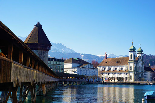 Chapel Bridge along the riverfront in Lucerne, Switzerland, with the Jesuit Church in the background.