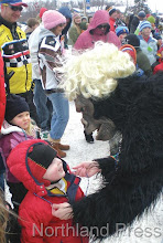 Photo: Three year old Mack Krakowski of Stillwater receives beads from a wandering  gorilla during the 36th annual Nisswa Jubilee Parade  - photo by Brenda Brodmarkle