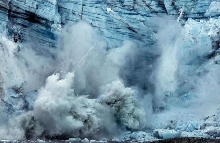 A tidewater glacier breaks off, or calves, on Margerie glacier in Glacier Bay, giving birth to several icebergs.