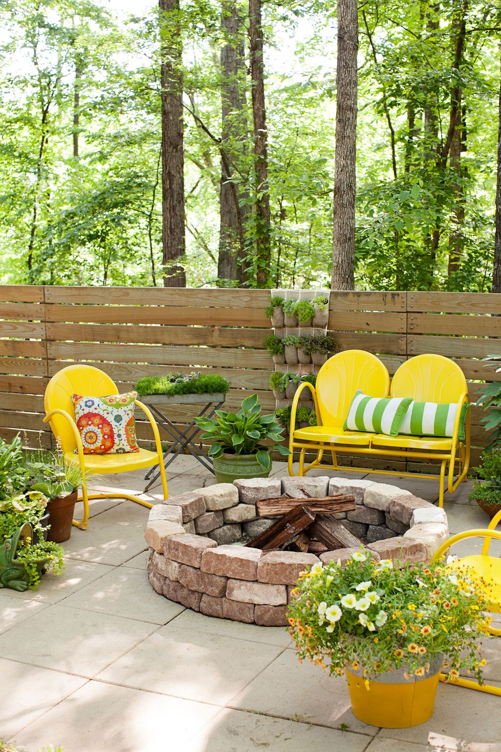 yellow outdoor furniture on stone patio in the woods