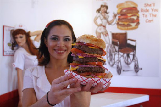 Heart Attack Grill waitress shows off the 'Quadruple Bypass Burger'