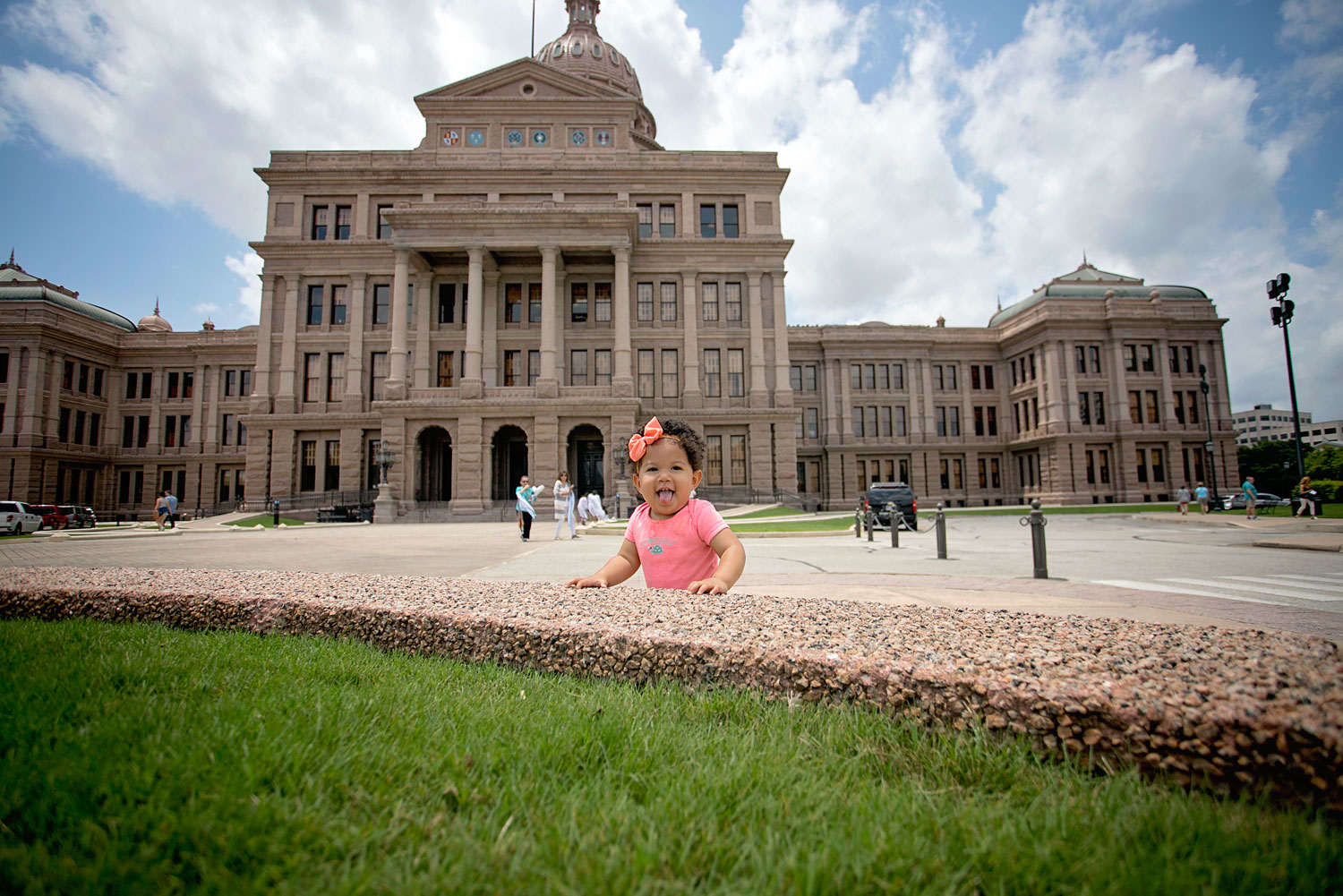 Biracial baby standing in front of the Texas state capitol building.