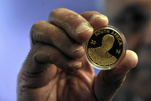 Ahmed Kathrada holding a coin launched by South African Mint and Nelson Mandela Foundation in 2014 in Johannesburg. Today some buyers of the coins are complaining that they have been deceived by Gold for Life who allegedly sell them the coins under the pretence of investment but only to find out later that they had been tricked by the company./ GALLO IMAGES