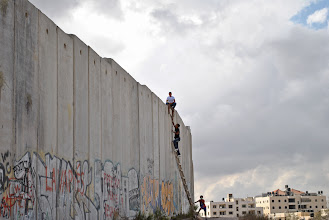 Photo: A young Palestinian uses a ladder to scale the wall at Qalandiya checkpoint.