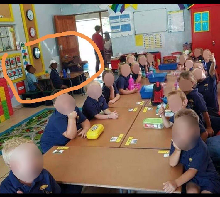 A picture of one of the grade R classes at Laerskool SchweizerReneke seemingly depicting white pupils seated separately from the black children
