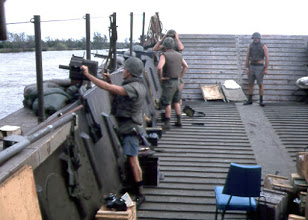 "Photo: Sometime in 1968 Mekong Delta on a troop pickup mission. TomTwitty on Honeywell Grenade Launcher.  ""Bad Ass  Area"" crew in the Well Deck with lots of ammo around and Sand Bags. We even had our flak jackets on....  Where were we?  Edit if you know.  Looks like Staff Sergeant Stan Cidlowski running the mission."
