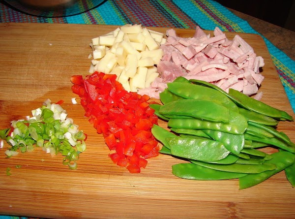 Add ham, swiss cheese, pea pods, scallion and red bell pepper to the tortellini.